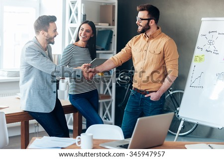 Good job! Confident young man standing near whiteboard and shaking hand to his colleague while young woman standing near them and smiling