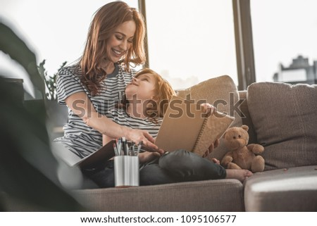 Good job. Full length portrait of smiling woman responding to picture painted by her child at home. Small happy kid looking on her mom anticipating for reaction