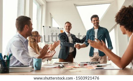 Good job Two cheerful colleagues shaking hands and smiling while having a meeting in the modern office