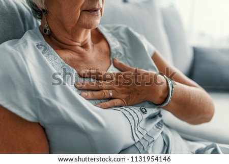 Good looking aged woman having heart attack. Woman is clutching her chest, acute pain possible heart attack. Heart disease. People with heart problem concept