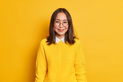 Good looking Asian schoolgirl happy to receive praise smiles gently has dimples on cheeks feels delighted dressed in casual knitted sweater isolated over yellow background. Emotions concept.
