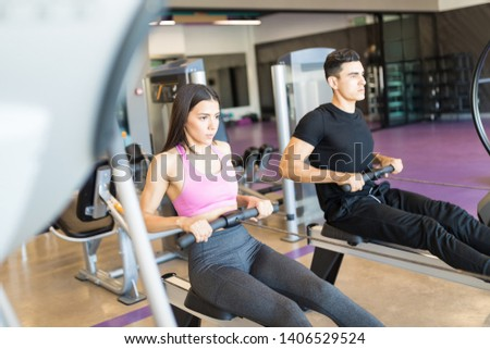 Good looking athletes training hard on rowing machines at health club