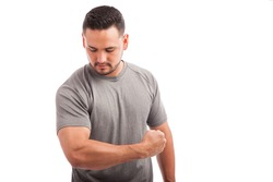 Good looking athletic young man showing his arm strength against a white background