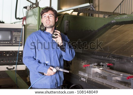 Good looking blue collar worker at machine in factory - stock photo