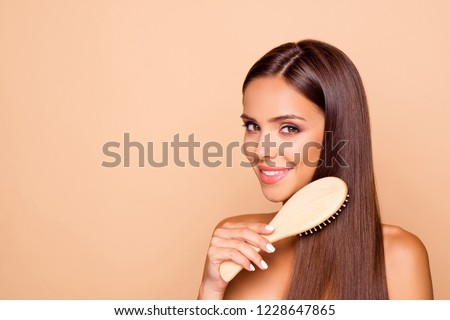 Good-looking brown-haired lady with her naked shoulders look at camera she combing hair with wooden brush teeth toothy smile isolated on pastel beige background with copy space for text make