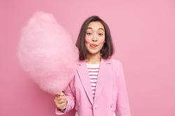 Good looking brunette Asian woman licks lips as holds appetizing sweet candy floss dressed in fashionable formal outfit isolated over pink background. Teenage girl with delicious cotton candy
