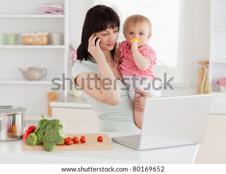 Good looking brunette woman on the phone while holding her baby in her arms in the kitchen