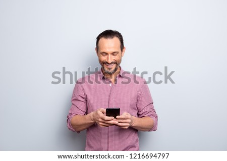 Good-looking cheerful man in casual wear look on cellular make beaming toothy hollywood smile isolated on light gray background