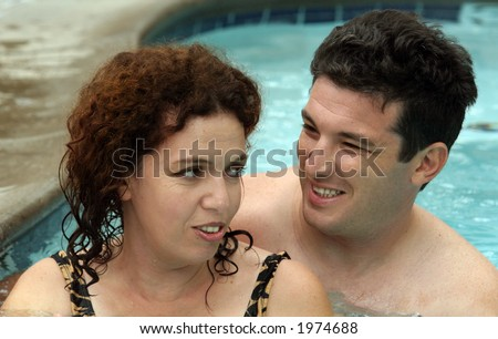 Good looking couple having good time in the pool