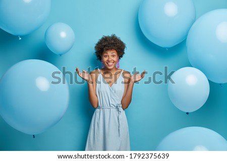 Good looking curly haired woman spreads palms, smiles sincerely, enjoys summer party, wears blue dress, stands against festive air balloons, has happy mood, isolated. Feminity, style, fashion concept