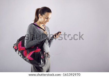 Good looking female athlete with a sports bag listening to music on her mobile phone Fitness woman in sports clothing going to gym on grey background