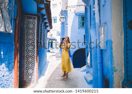 Good looking female with professional camera making fotos in colorful city - Morocco testing new equipment, woman photographer taking pictures of old streets around unesco heritage during vacations