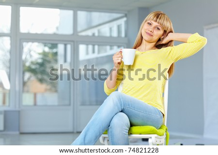Good looking girl sitting on the chair and relaxing drinking something