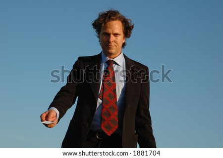 good looking guy in black suit, handing over his business card, shot from the waist up