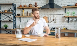 Good looking handsome bearded man is sitting in the kitchen drinking morning coffee with cereals and milk. reading morning press, looking aside Healthy food. Diet. Healthy lifestyle.