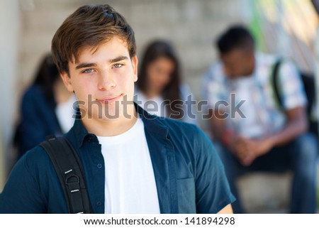 good looking highschool boy with friends on background
