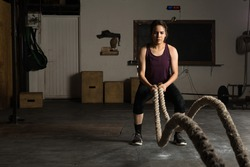 Good looking Hispanic young woman doing battle ropes exercises in a cross training gym
