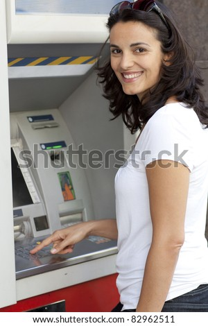 Good-looking latin woman enters the PIN number at the ATM - stock photo