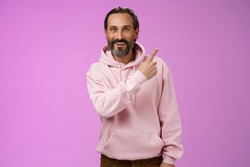 Good-looking lucky energized happy mature 50s man grey hair in trendy hipster hoodie pointing upper right corner amused telling you interesting news smiling white teeth thrilled joyfully look camera