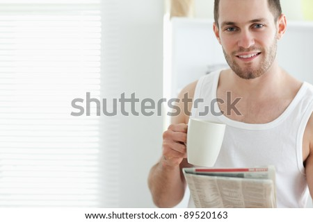 Good looking man drinking tea while reading the news in his kitchen