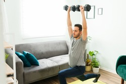 Good-looking man in his 30s doing leg plunges while raising wieghts above his head. Latin man exercising in the living room