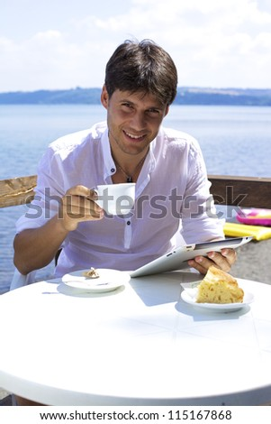 Good looking man relaxing while reading electronic tablet on a beautiful lake
