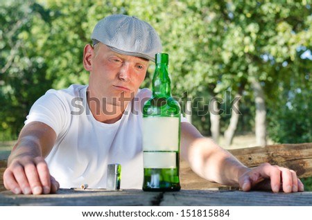 Good-looking man wearing a natty cap with a drinking problem sitting at a table in the park staring morosely at his bottle of liquor standing on the table