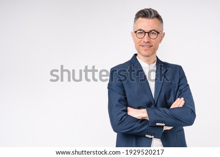 Good-looking middle-aged businessman with arms crossed isolated in white background