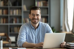 Good-looking millennial office employee in glasses sitting at desk in front of laptop smiling looking at camera. Successful worker, career advance and opportunity, owner of prosperous business concept