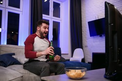 Good-looking modern positive 30-aged guy with well-groomed beard savoring chipps during emotional review of favourite football team's game on tv at home
