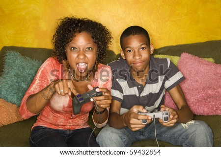 Good-looking mom and son Playing a Video Game with Handheld Controllers