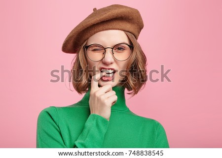 Good looking old fashionable woman blink eye and keeps finger between teeth, flirts with handsome man, expresses her sympathy. Confident female student nerd with attractive appearance isolated on pink