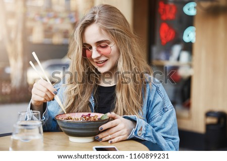 Good-looking popular lifestyle blogger gazing at bowl with asian food, ordering ramen for first time, gathering courage to try spicy meal, holding chopsticks, wearing denim jacket and sunglasses