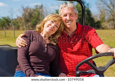 Good-looking retired couple riding their property in an all terrain utility vehicle.