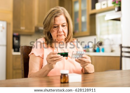 Good looking senior adult woman looking at her pills' expiration date sitting in the kitchen