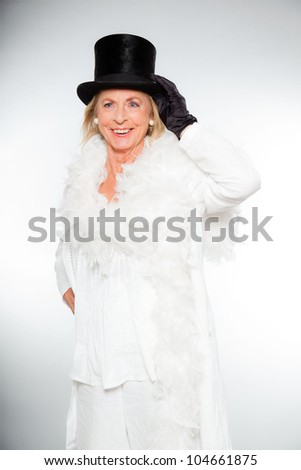 Good looking senior blond woman isolated on white background. Dressed in white and wearing black hat and white boa. Expression and emotion. Studio shot.