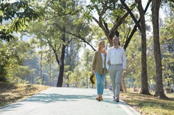 Good looking senior couple walking along small street in public park in the moring after retirement. Healthy senior or happy elder couple concept.