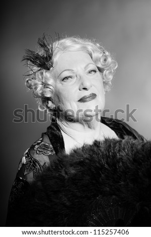 Good looking senior woman glamour vintage style. Holding a black fan. Black and white studio shot. Short blonde curly hair. Chic look. Dressed in black.