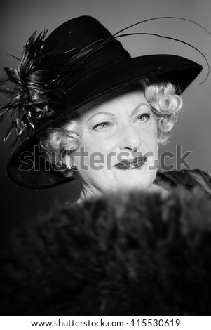 Good looking senior woman glamour vintage style. Wearing a black hat. Holding a black fan. Black and white studio shot. Short blonde curly hair. Chic look. Dressed in black.