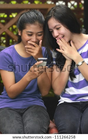 Good looking southeast asian girls sharing information on a smartphone with happy and surprise expression