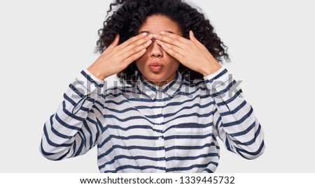 Good-looking stylish African American young woman in striped shirt, covering eyes with palms and making air kiss, waiting to be kissed. Playful dark-skinned  female playing hide, seek and peek a boo.  #1339445732