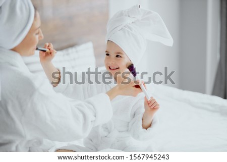 good-looking woman and cute lovely little daughter sit wearing white bathrobe and towel after shower on white bed. holding brushes and doing make-up for each other. beauty procedures at home ストックフォト ©