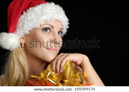 Good-looking woman dressed as Santa on a black background