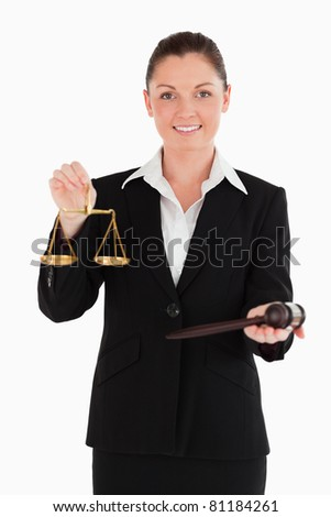 Good looking woman in suit holding scales of justice and a gavel while standing against a white background