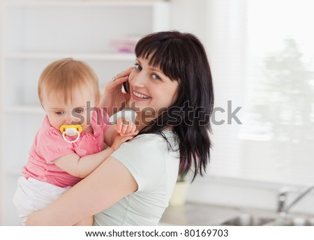 Good looking woman on the phone while holding her baby in her arms in the kitchen