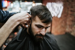 Good looking young adult man getting a hair and beard styling and dressing treatment by professional hairstylist.