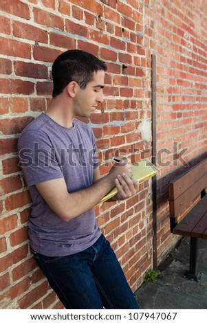 Good looking young adult man writing on a yellow pad of paper by a brick wall outdoors wearing a purple shirt.