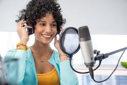 Good looking young black female making an online podcast recording for her online show. Attractive millennial African American business woman using headphones front of microphone for a radio program.