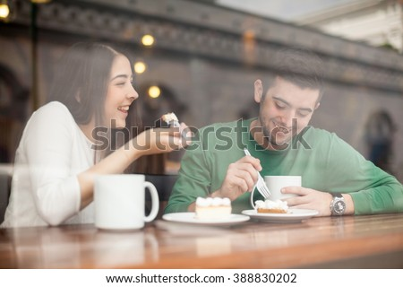 Good looking young couple laughing and having a good time on a date in a coffee shop