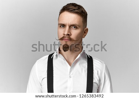 Good looking young groom with stylish neat haircut, hipster mustache and goatee beard posing isolated wearing smoothly ironed white shirt and black suspenders on wedding day, having serious look ストックフォト ©